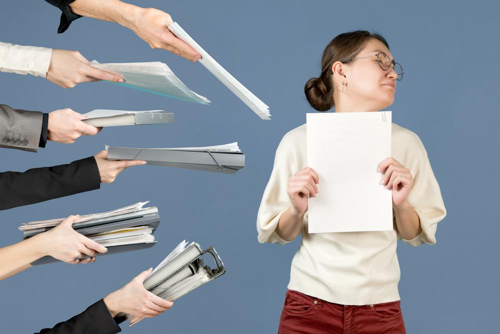 複数人から書類を渡されて困っている女性